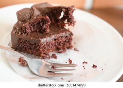 Chocolate fudge cake on white plate,bitten off.