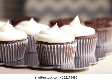 Chocolate gourmet cupcakes with sprinkles and buttercream frosting - side view