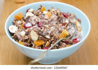 Chocolate granola with nuts, dried fruit and milk on a wooden board, closeup horizontal