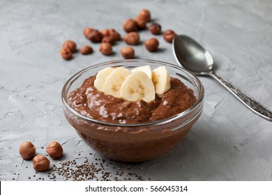 chocolate hazelnut chia pudding with banana in a glass bowl on gray concrete background
