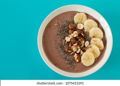 Chocolate hazelnut smoothie bowl topped with sliced banana, chia seeds, chopped chocolate, nuts and sesame seeds.