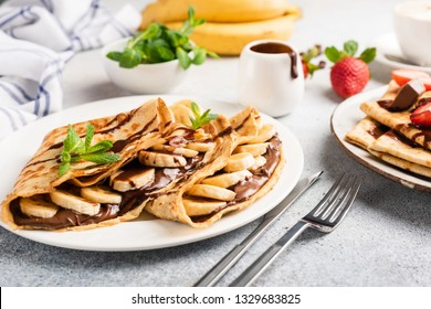 Chocolate hazelnut spread and banana filled crepes on plate. Tasty crepes or blini with sweet sauce and fruits. Closeup view