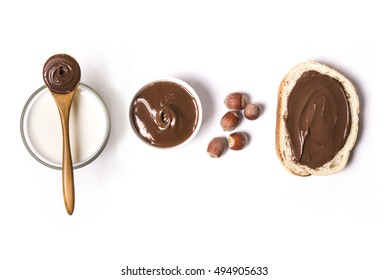 chocolate and hazelnut spread with milk and hazelnuts over white background. top view