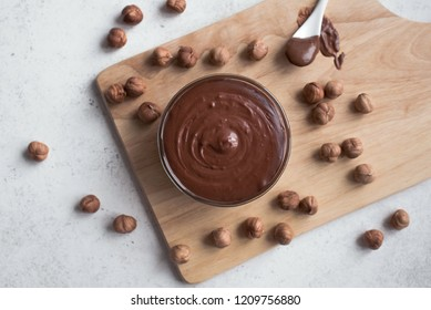 Chocolate Hazelnut Spread on white background, top view, copy space. Homemade chocolate spread with hazelnuts.