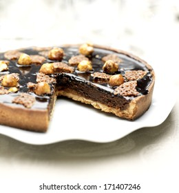 Chocolate and hazelnuts pie on a plate