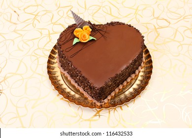 Chocolate heart cake on golden background