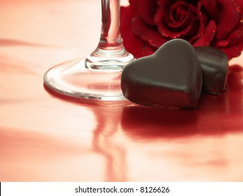 Chocolate hearts with champagne glass on reflective red background