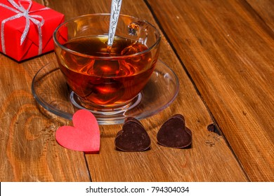 Chocolate hearts with a cup of tea on a wooden table. Close-up.