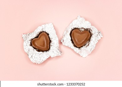 Chocolate hearts in foil on pink background
