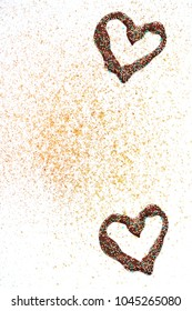 Chocolate hearts and golden glitter on white background