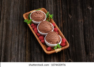 Chocolate ice cream with bowl on wooden background