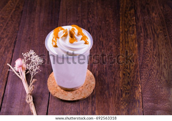 Chocolate ice cream in a cup on a grey wooden table wall background with copy space .