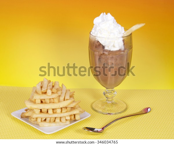 Chocolate ice cream in glass cup with whipped cream and square white plate of symmetrically stacked french fries. Food fad or new trend. Sweet and salty. pink and yellow textured background.