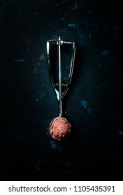 Chocolate ice cream in metal spoon for ice cream, dark background, top view
