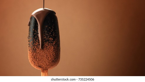 chocolate ice cream on a stick and liquid chocolate covered it. Different chocolate textures. on brown background