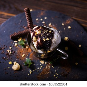 Chocolate ice cream. Some chocolate wafles. Green leafs. Blur black wooden dark background. Delitious food. Food concept. Beaity food. Healthy. Eating Concept.