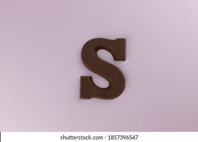 Chocolate Letter of the alphabet S on the pink background