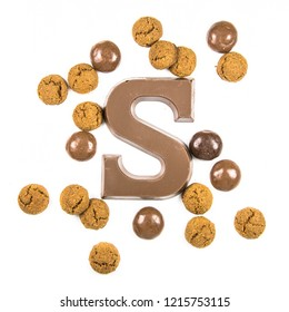Chocolate letter S with bunch of scattered chocolate pepernoten cookies from above on white background for annual Sinterklaas holiday event in the Netherlands on december 5th