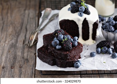 Chocolate loaf cake sliced decorated with frosting and berries