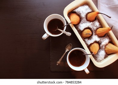 Chocolate loaf cake with whole pears baked inside and two cups coffee on dark background. Top view