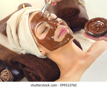 Chocolate Luxury Spa. Facial Mask. Beautiful young woman relaxing in beauty spa salon, applying chocolate face mask.