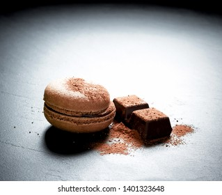 Chocolate macaron at the black background, close up