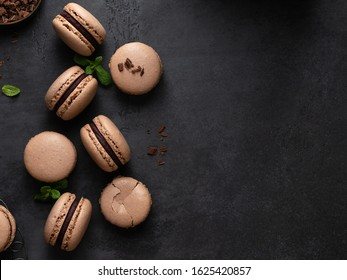 Chocolate macarons with chocolate ganache filling and mint leaves isolated. French meringue cookies macaron. Top view. Dark background. Copy space.
