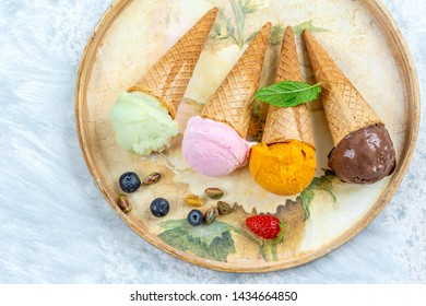 Chocolate, mango,lemon and candyfloss,Ice cream in the cone i a old tray with fresh berry, on white background