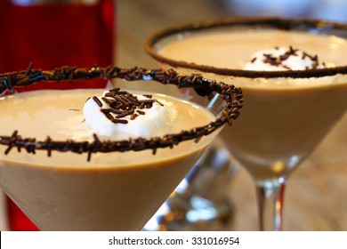 Chocolate martini garnished with chocolate powder on the rim and whip cream and sprinkles