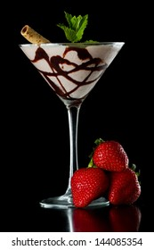chocolate martini served isolated on a black background with chocolate swirl and a wafer stick