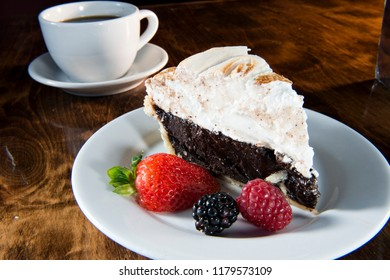 Chocolate Meringue Pie with Strawberry, Blackberry, Raspberry and Coffee Served on a White Plate