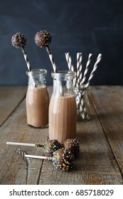 Chocolate milk with cake pops on table