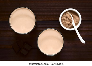 Chocolate milk drink in glasses, chocolate or cocoa powder on the side, photographed overhead with natural light (Selective Focus, Focus on the chocolate drinks)