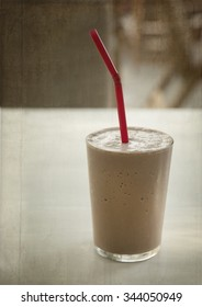 Chocolate milkshake in a glass with red straw.  Wooden texture effect.