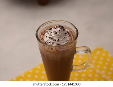 chocolate milkshake in glass with whipped cream on wooden table. Selective Focus.