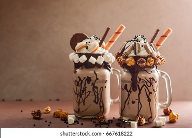 "Chocolate  milkshake with ice cream and with whipped cream, marshmallow, sweet popcorn, cookies, waffles, served in glass mason jar. ""Freak or crazy"" sweet shake."