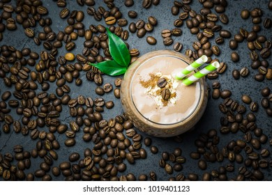 Chocolate mocha breakfast smoothie and coffee beans on dark concrete background. Top view, space for text, close up.