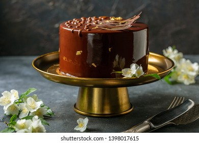Chocolate mousse cake in mirror glaze on a bronze stand, on a dark textured background, selective focus.