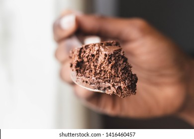 Chocolate mousse dessert on silver spoon isolated on white background. Delicious Texture Close Up in African American hand