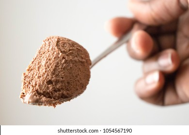 Chocolate mousse dessert on white background on the Spoon Texture Close Up in African American hand