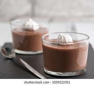Chocolate mousse in a glasses on a black stone background.