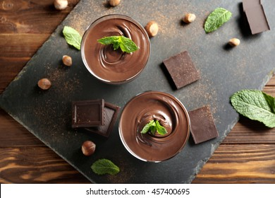 Chocolate mousse with mint in portion glasses on slate cheese board