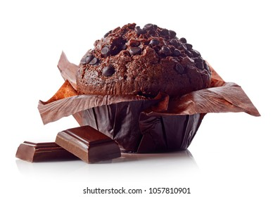 Chocolate muffin in brown paper with chocolate pieces isolated on white background