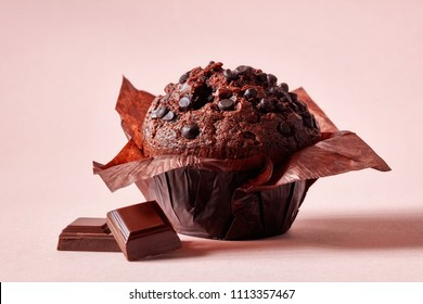 Chocolate muffin in brown paper with chocolate pieces on pink background