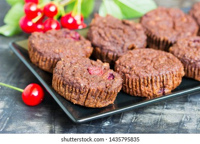 Chocolate muffin with fresh cherries on a plate