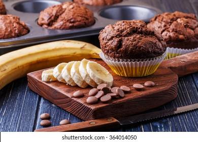 Chocolate muffins with banana on dark background, selective focus.