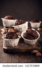 Chocolate muffins with banana in white paper cups on dark wooden background. Party food concept.