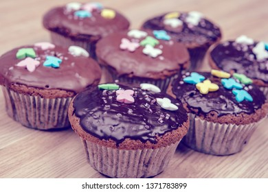 chocolate muffins with colorful decoration on wooden ground