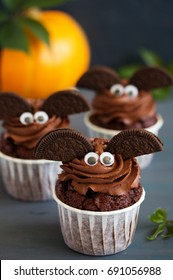 Chocolate muffins, with a chocolate cream in the form of bat on Halloween.