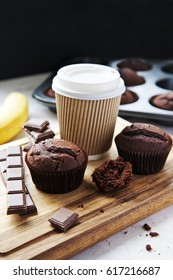 Chocolate muffins with cup of coffee to go, banana and chocolate bar.